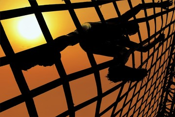 Man climbing a net during sunset. Spartan and gladiator race concept.