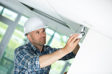 male technician installing camera on wall with screwdriver