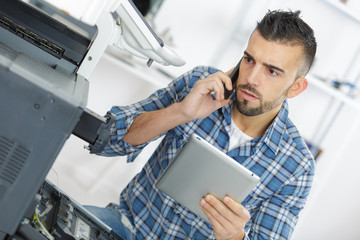 technician seeking help on the phone while repairing printer