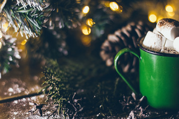 An old vintage green mug with cocoa and marshmallows on the Christmas lights background on the wooden surface