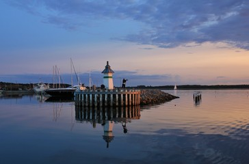 Small lighthouse and sailing boats at sunset.