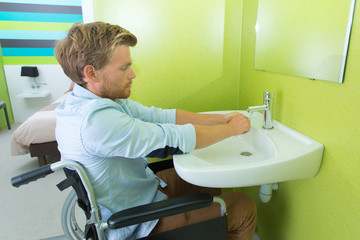 disabled young man in the wheelchair when washing hands