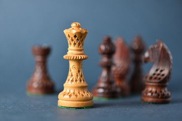 White chess queen in front of black pieces