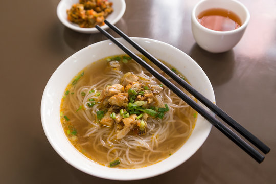 Dish of Burmese Shan noodles soup on a table with chopsticks in Myanmar, viewed from slightly above.