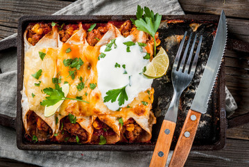 Mexican food. Cuisine of South America. Traditional dish of spicy beef enchiladas with corn, beans, tomato. On a baking tray, on old rustic wooden background. Top view
