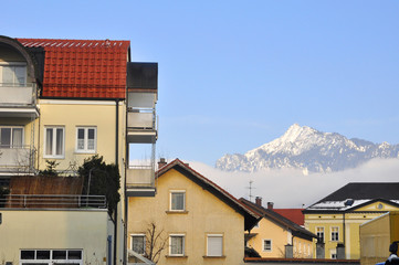 Yellow houses with a mountain in the background.