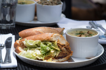 Lunch combo included crispy fresh sandwich with lettuce, sauce and meat and soup on the side served on a table outside.