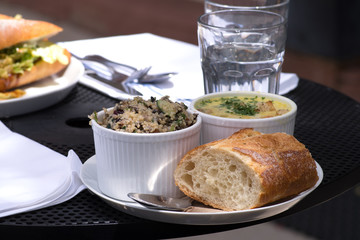 Delicious business lunch served on the outside table. Lunch included healthy quinoa salad,fresh baguette and soup. Close-up.