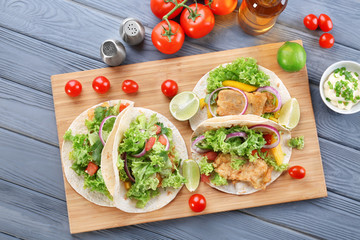 Wooden board with delicious tacos on kitchen table