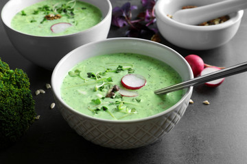 Bowl with delicious and creamy broccoli soup on grey background