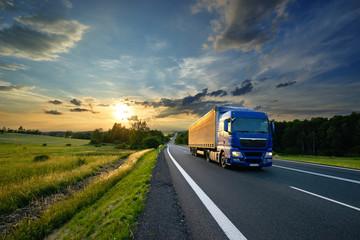 Fotobehang - Blue truck driving on the asphalt road in rural landscape at sunset