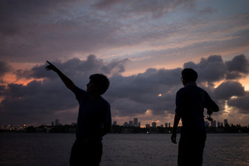 The Miami skyline is seen in the background as boys fish ahead of the arrival of Hurricane Irma in Miami Beach, Florida