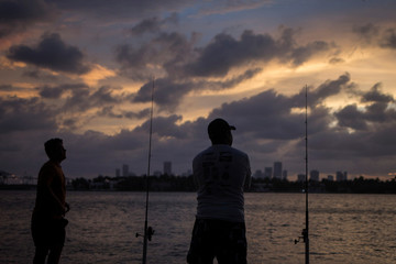 The Miami skyline is seen in the background as men fish ahead of the arrival of Hurricane Irma in Miami Beach, Florida