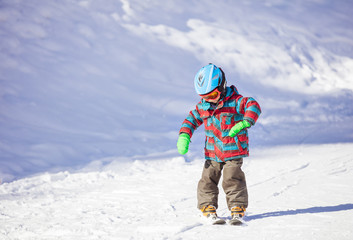 Little boy learning to ski downhill
