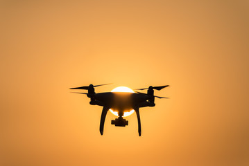 Modern technological background - silhouette of flying drone in glowing red sunset sky,Silhouette flying drone on sunset