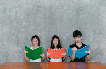 Young students asian together group teenager smile with school folders reading book at high school university campus college knowledge center for study learning in summer,copy space the top.