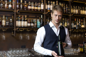 Handsome sommelier man promoting bottle of wine in restaurant, Man present Wine to Customer, Man with Sommelier Concept.