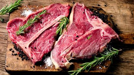 Deurstickers Steakhouse Raw fresh meat t-bone steak and seasoning on wooden background