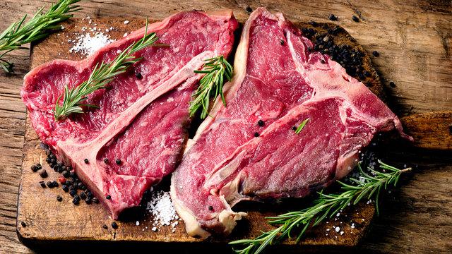Raw fresh meat t-bone steak and seasoning on wooden background