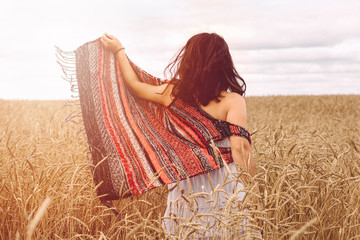 a young girl in a field of wheat. warm solar toning