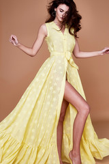 Sexy beauty woman pretty face tan skin wear yellow silk dress long skinny body shape makeup cosmetic summer collection studio catalog brunette curly hair clothes for date meeting walk beach fashion.