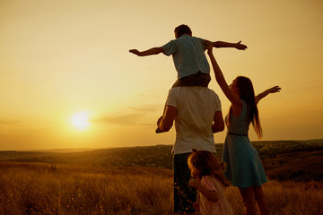 Happy family in the field at sunset.