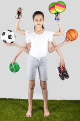 Smart girl in a white T-shirt with six hands standing on the green grass and holding sports equipment. Sport concept with many hand. Grey background.