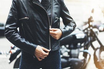 Girl unfastens black leather jacket on background motorcycle in sun flare atmospheric city, hipster biker female hands closeup, motorbike lifestyle, traveler planing route in summer holiday