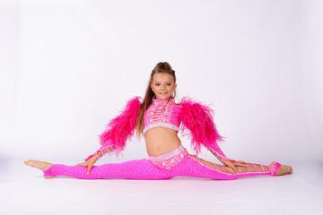 Flexible little girl gymnast doing acrobatic exercise on white background
