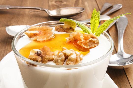 yogurt with walnut and acacia honey in a glass