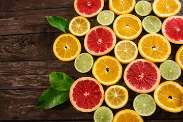slices of oranges, limes, grapefruit and lemons. Over wood table background with copy space.