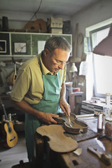 Artisan shaping a violin