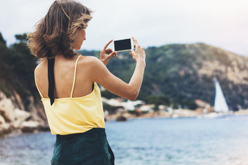 Hipster girl photograph on smart phone gadget in sand coastline, mock up of blank screen. Traveler using in female hand mobile on background seascape horizon. Tourist and blue sun ocean, lifestyle