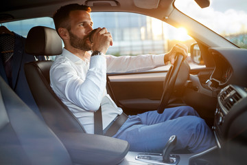 businessman driving car while drinking a cup of coffee.