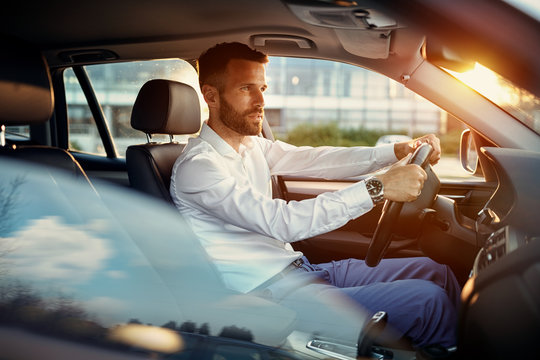 Young businessman driving car.