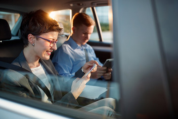 smiling business woman calling smartphone number in car.