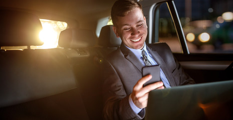 Businessman work on late night in back seat of car.