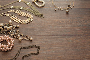 Decorative composition of women's jewelry on wooden dark background.
