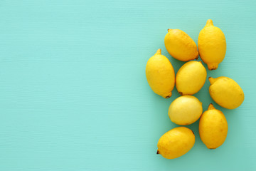 Top view of fresh lemons over blue wooden background