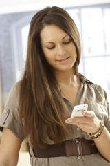 Closeup portrait of young woman with mobile