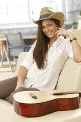 Happy guitar player sitting on sofa