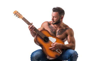 Portrait of muscular man with tattoo playing guitar. Isolated on white background. Full length shot