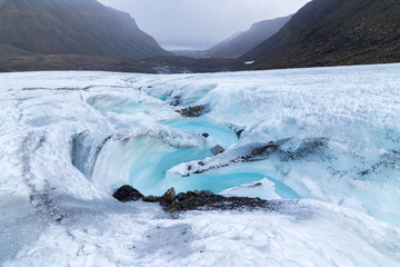 Photo sur Plexiglas Glaciers Meltwater stream flowing from Longyear glacier moraine in the Arctic, Svalbard. Thawing of glaciers and global warming problem.