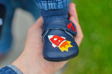 Hand of mom holding baby's feet. The child in a shoe with the spaceship label.