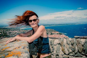 Femme jouant avec le vent en haut du Fort Saint-Elme