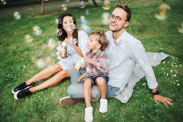 Happy young family playing with bubble wands in park outdoors