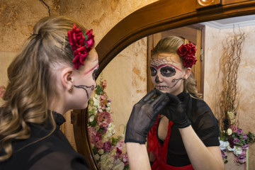 Girl in a suit and make-up for a Halloween party near the mirror
