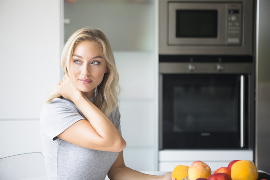 Young woman eating fruit in the kitchen