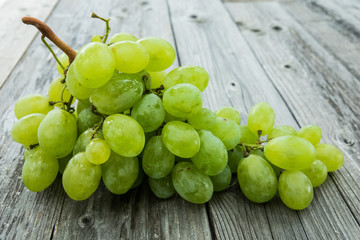 bunch of ripe and juicy green grapes close-up on a wood background