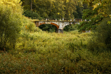 Ancient ruined brick bridge in the forest. Serednikiovo, Moscow region, Russia. Ancient brick bridge in the overgrown park.